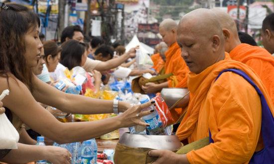 Люди подносят еду монахам
