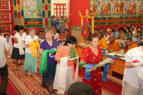 Люди подносят цветы Будде