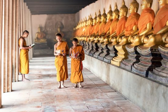 монахи около статуй Будды