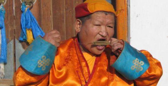 буддийский монах играет на варгане