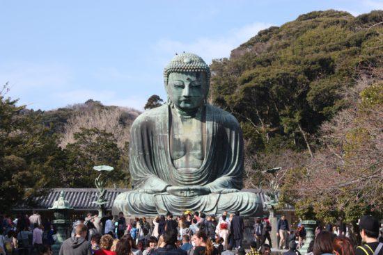 верующие буддисты и статуя