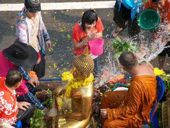 Тайцы поливают водой друг друга и будду