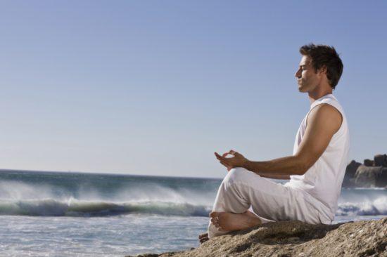 мужчина медитирует на берегу