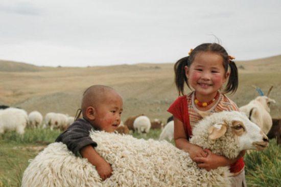 девочка и мальчик обнимают овцу