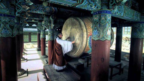 Монах бьет в барабан в монастыре Хэинса